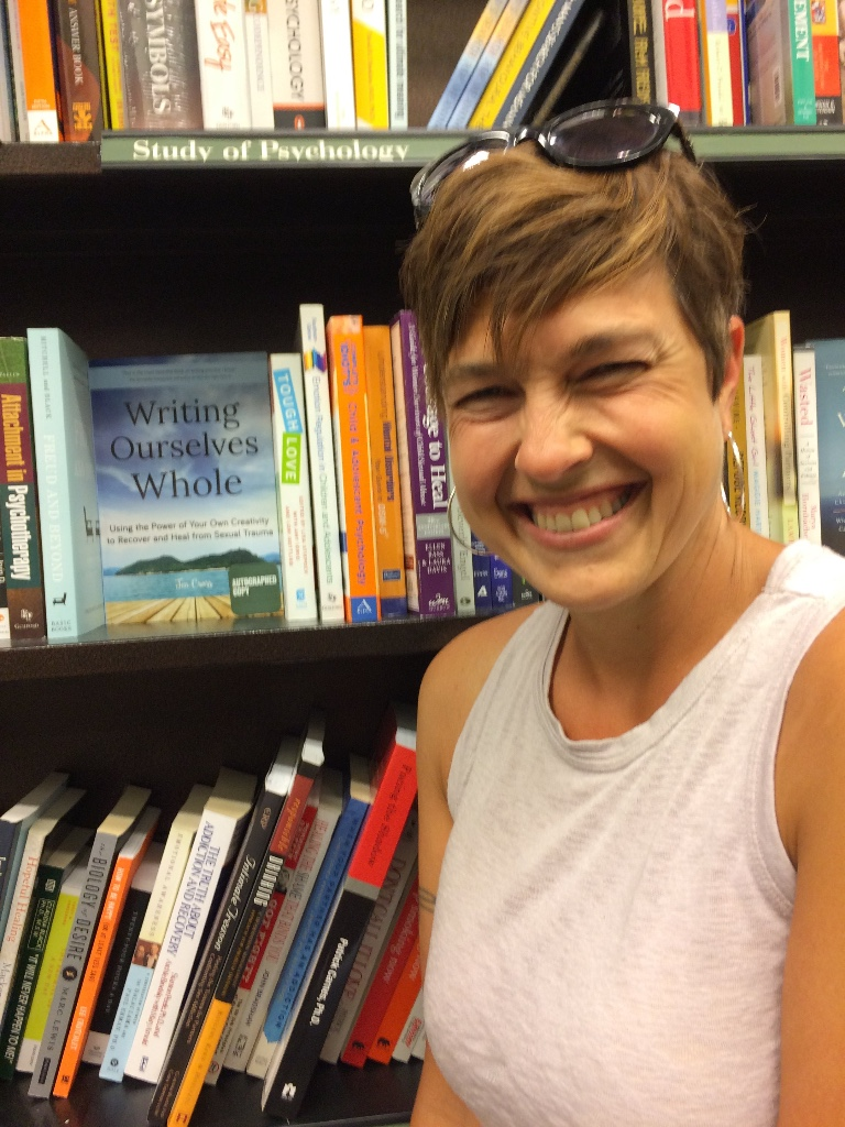 Jen smiles big next to the Writing Ourselves Whole book on a bookstore's shelves!