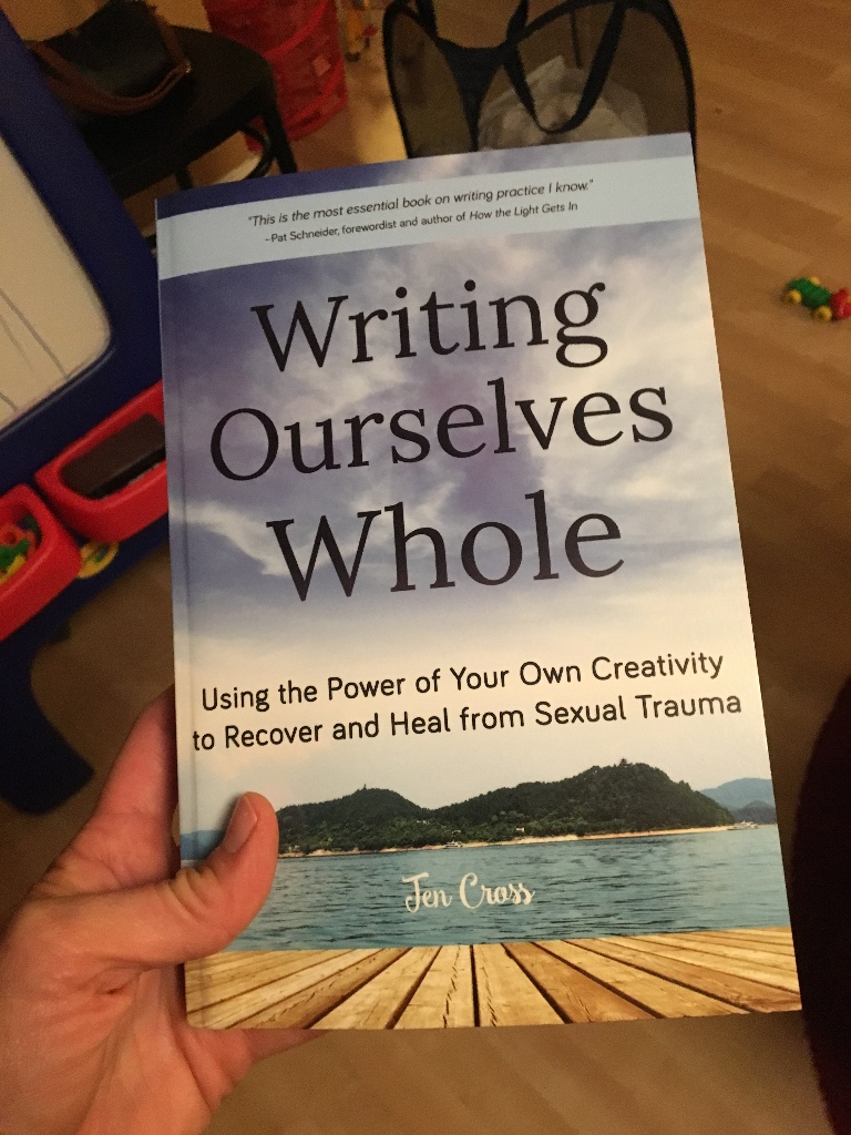 Cover of Writing Ourselves Whole book, held in a hand over toys and a wooden floor