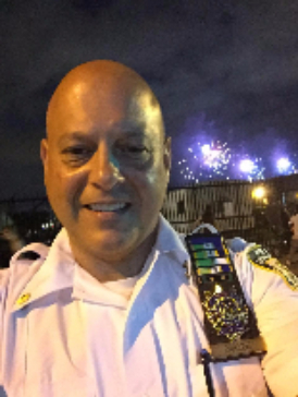 Deputy Inspector Dan Carione standing with fireworks in the sky behind him.