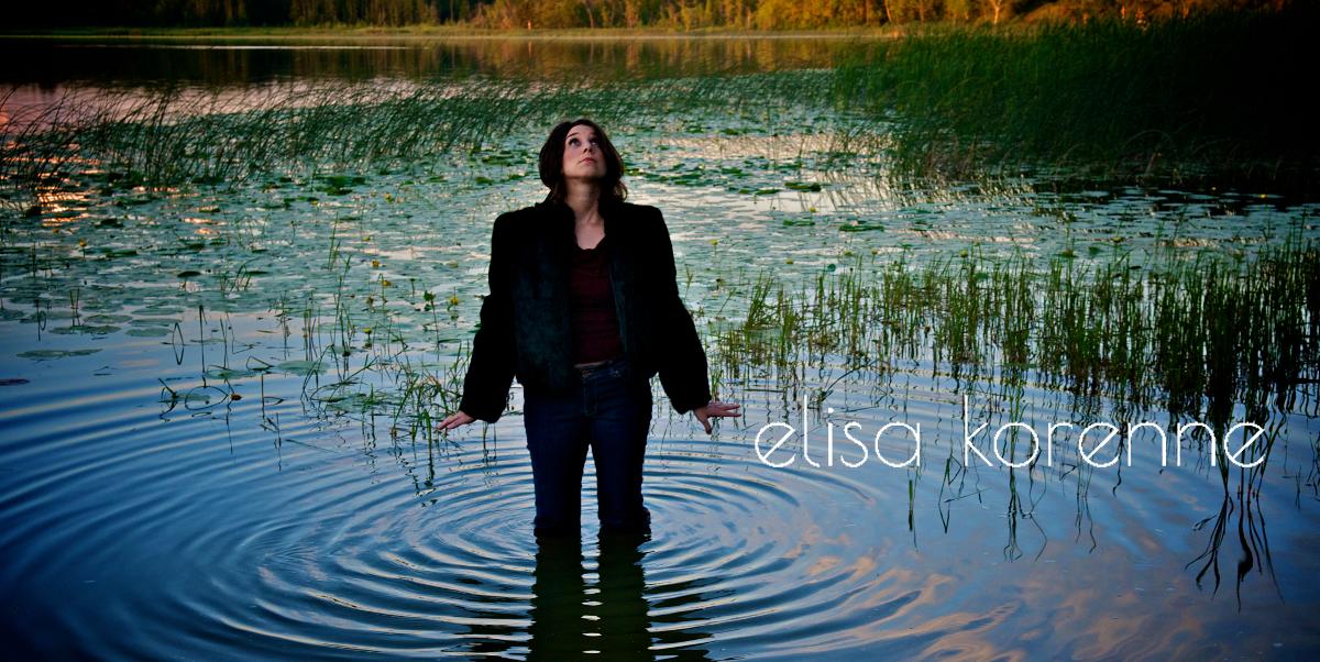 Photo of fur-clad Elisa Korenne wading in lake and staring at sky