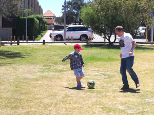 Arek Zoltowski & his son play soccer together in a park