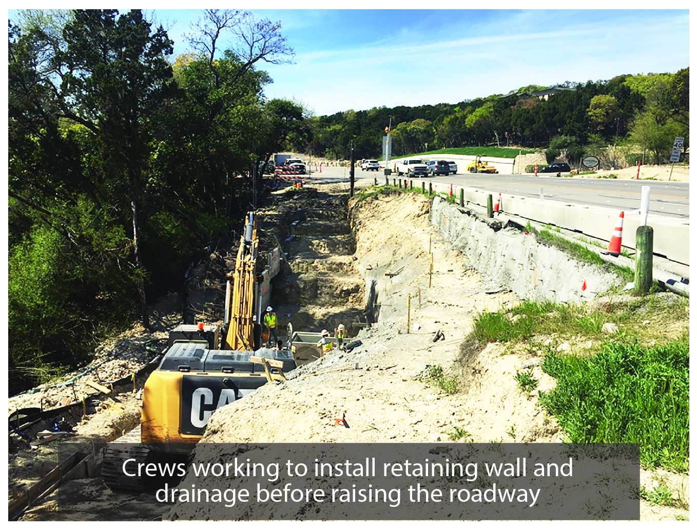 Crews working to install the retaining wall and drainage by road