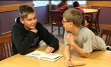High school student and elementary school student reading together.