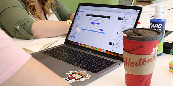 Two people working together around a laptop that has a Canadian Mountie sticker on it.