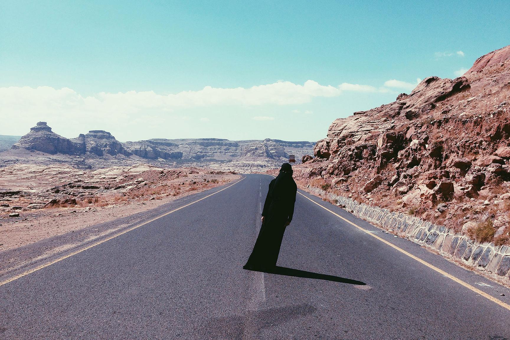Une femme qui porte un voile noir se tient debout au milieu d'une route dans un paysage désertique.