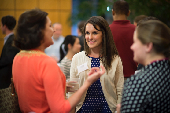 Employers and MBAs smiling and talking at a social gathering