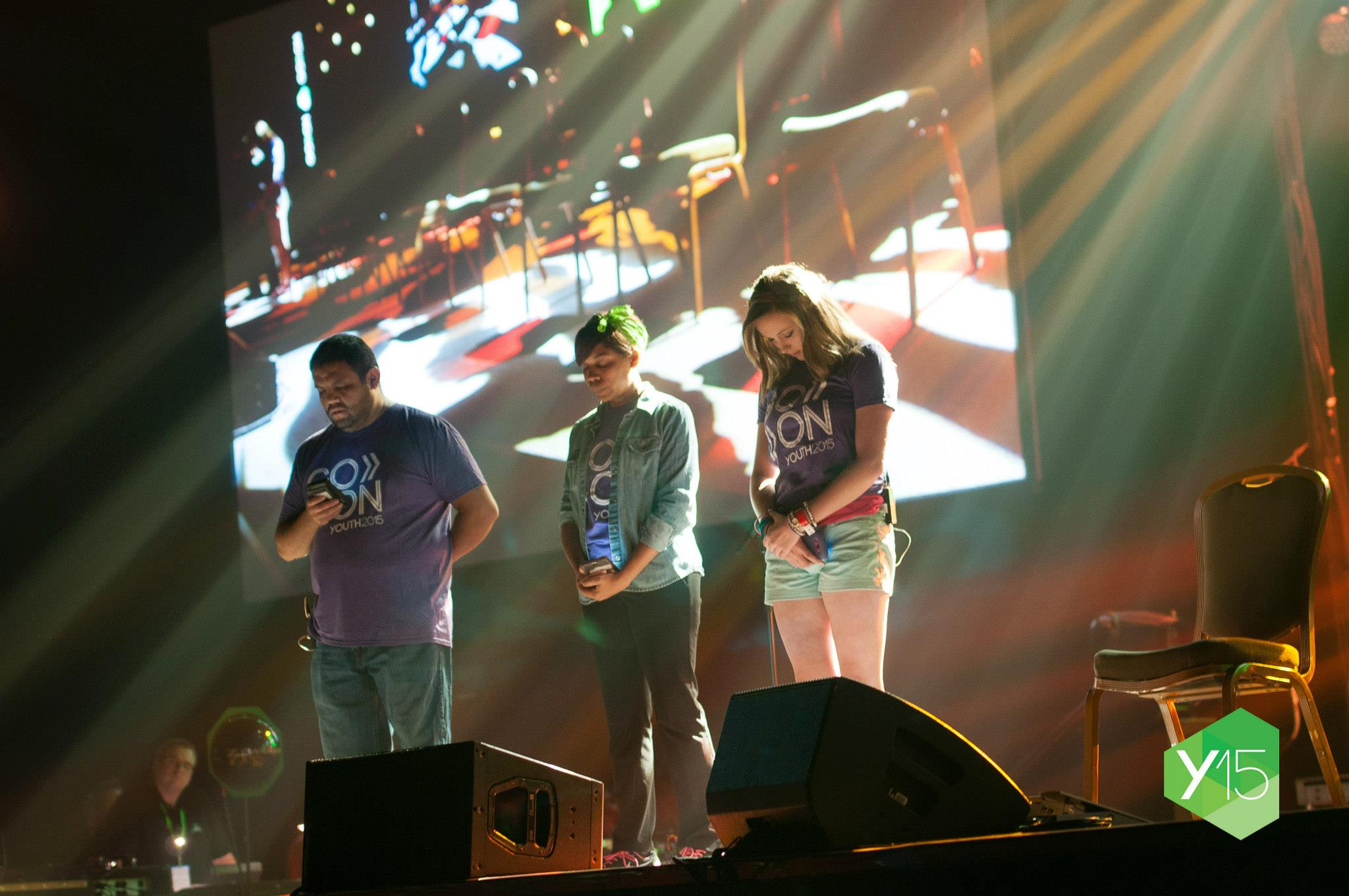 Y15 Design Team members (left to right) Miguel Padilla, Sabrina Short, and Allie Wainwright in a moment of prayer at the beginning of opening night's worship
