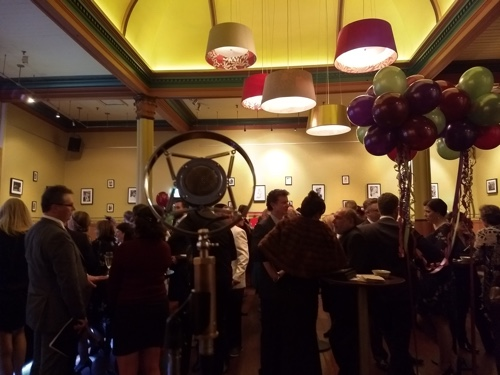 Audience mingling at corporate event. The Greg Poppleton trio creates 1920s background music