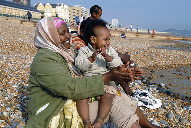 "Photograph by Howard Davies entitled ""Oromo family, Brighton 2007"" focusing on a mother and young child smiling and clapping on Brighton beach."