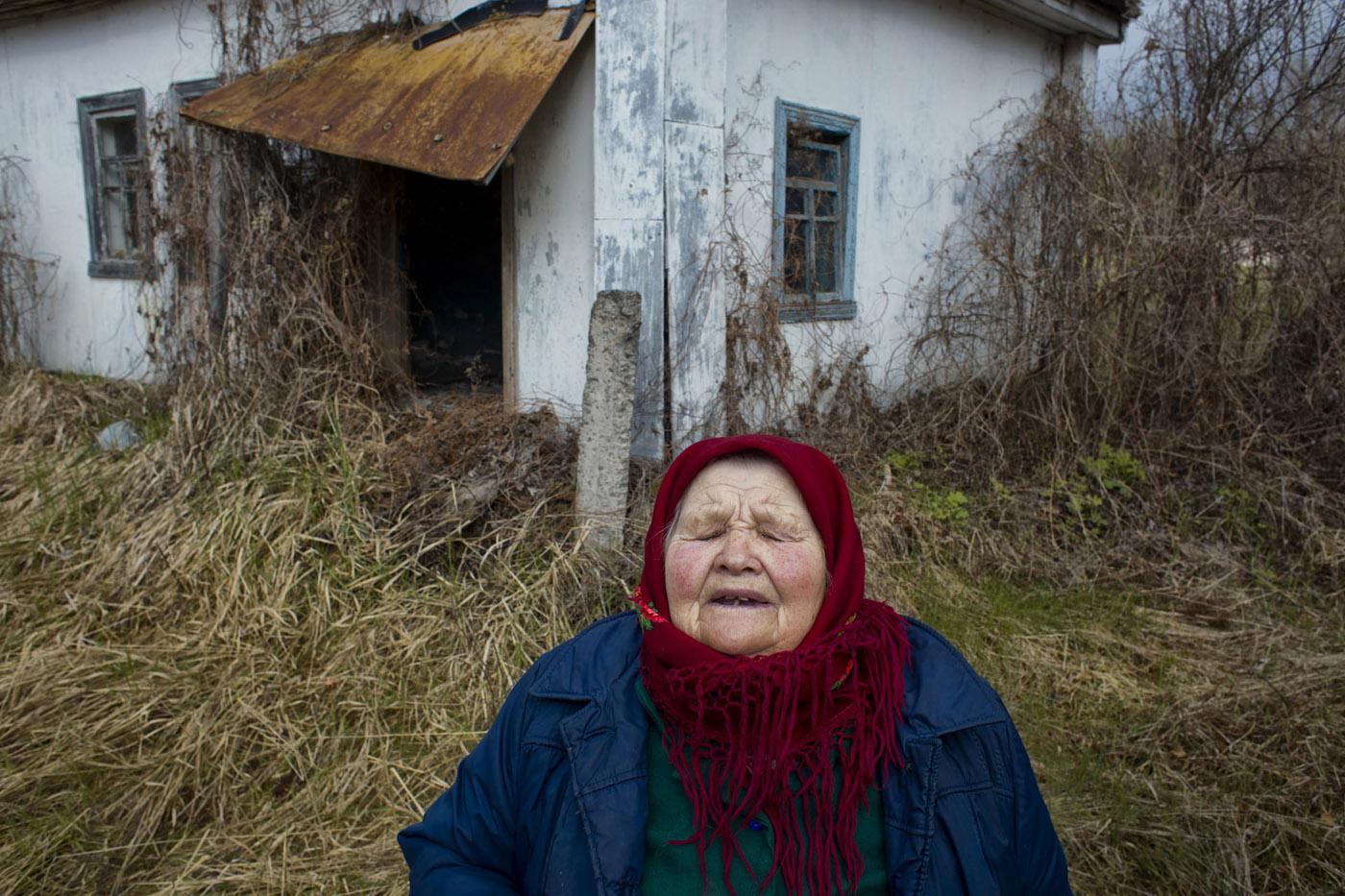 Anastasiya Patukh is seen in front of her house in Paryshiv - half abandoned village inside the Chernobyl's exclusion zone. Now she lives in Kovaln village. Photo by Maciek Nabrdalik / VII.
