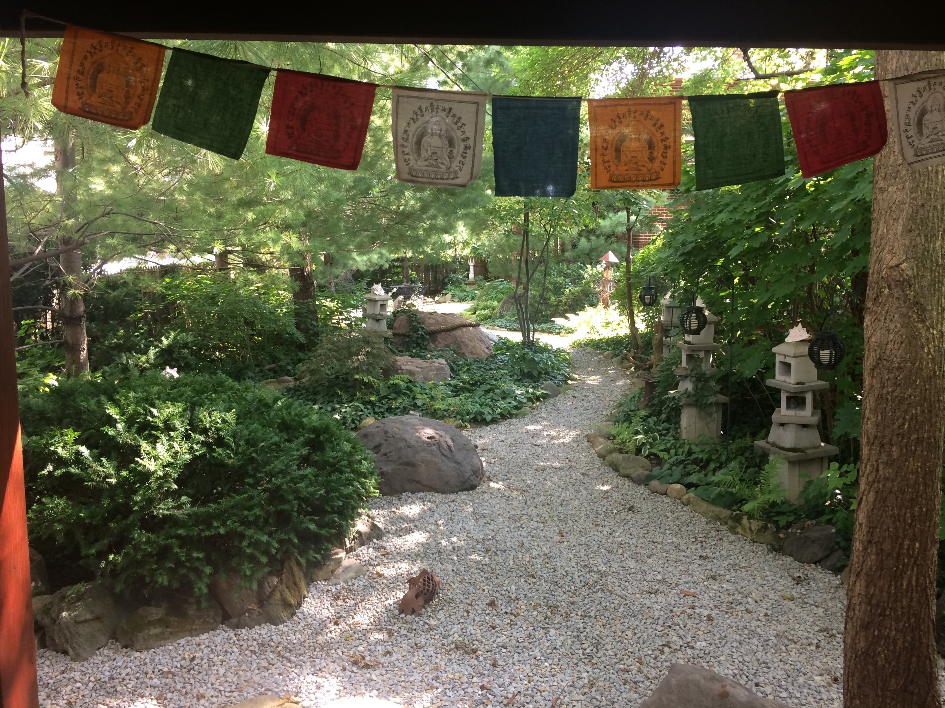 Photo of entrance to urban garden with gravel pathway and prayer flags