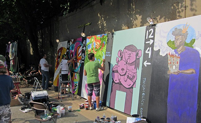 photo of artists working on canvasses at the Urban Scrawl event in Franklinton