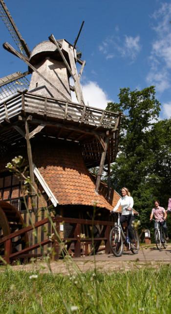 """Fietser voor de molen """"Hüvener Mühle"""" tijdens een fietstoch op de EmslandRoute"""