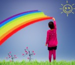 Little girl coloring a rainbow in the sky