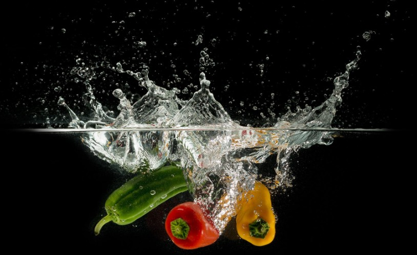 PhotoPeppers and a zucchini are plunging into water and splashing wildly.