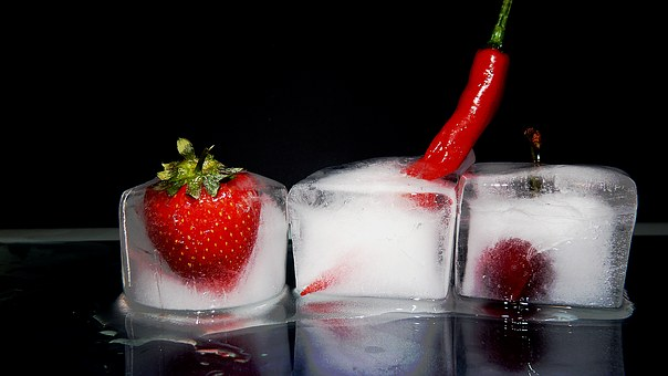 3 ice cubes filled with a strawberry, a chili, and a raspberry.