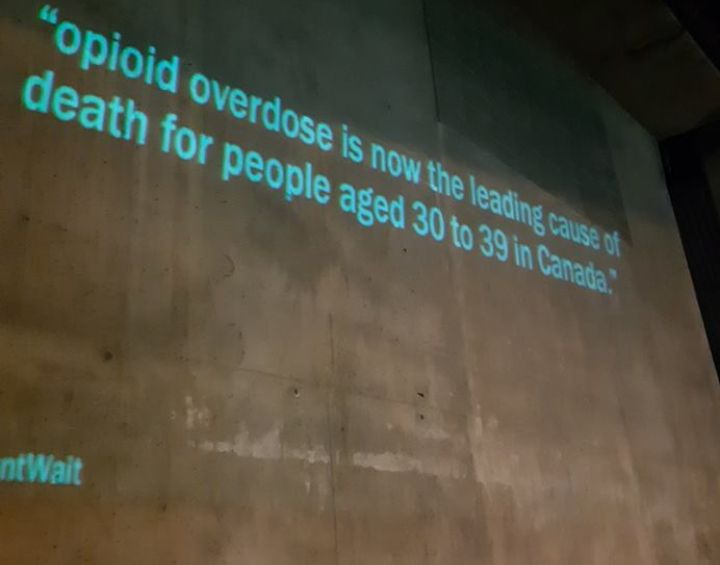 """Wall that has text projected on it: """"opioid overdose is now the leading cause of death for people aged 30 to 39 in Canada"""" and # CantWait"""