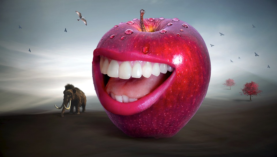 We are talking. Image of a smiling red apple with human teeth.