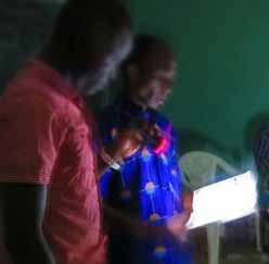 A pastor leads a Christian meeting by flashlight at damaged church building in Niamey, Niger. (RUN International)