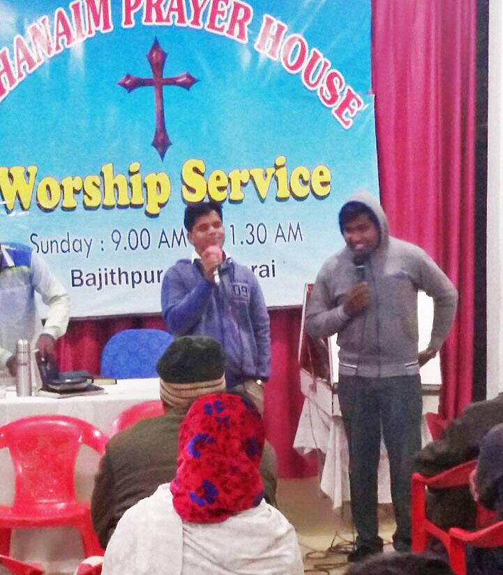 Pastor Ajay Kumar (in blue) and a student from Bethany Bible College, in Kerala state, at a prayer service. (Morning Star News)
