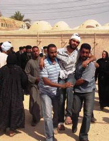 Christians assist a wounded Copt in Al Dabaya outside Luxor, Upper Egypt. (Morning Star News photo)