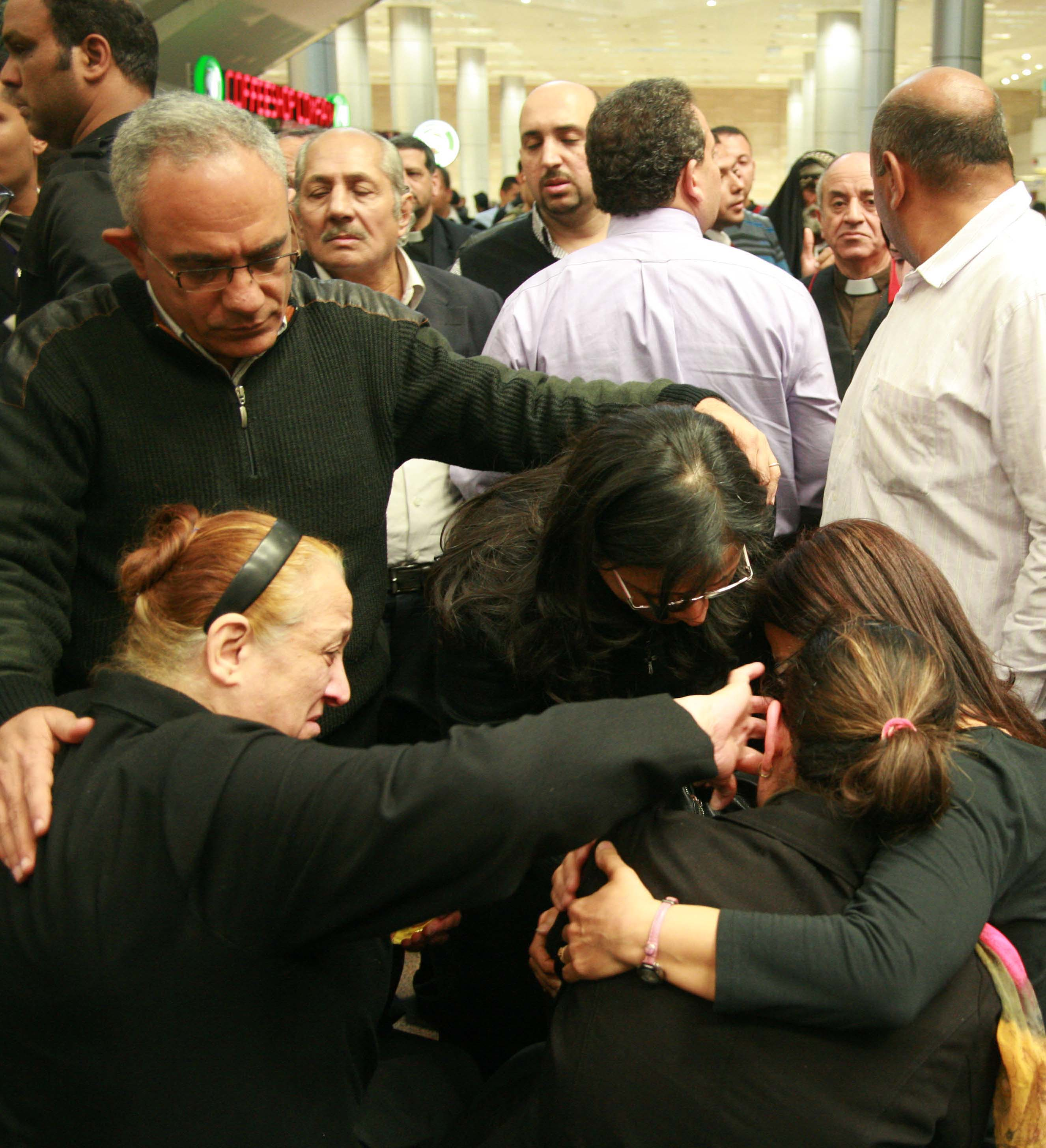 Ezzat Hakim Atallah's widow, Ragaa Nagah (with ponytail), collapses with grief upon arrival to Cairo's airport. (Morning Star News photo)