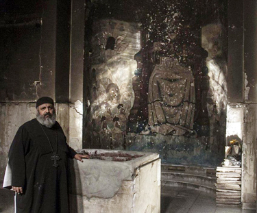 Priest examining damage in church building in Minya Governorate, Egypt. (Watani)