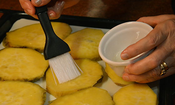 brushing sweet potato slices with oil