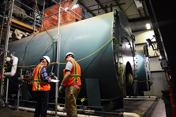 Vit Plant workers inspect the large boilers in the steam plant facility.