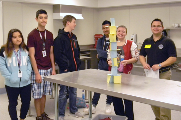 A Vit Plant worker poses with high school students during a Junior Achievement classroom session.