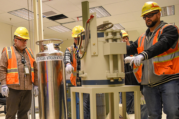Employees safely install a gamma-ray detector shield inside the Waste Treatment and Immobilization Plant's Analytical Laboratory.