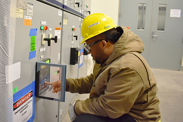 An employee checks electrical equipment in the Low-Activity Waste Facility switchgear building.