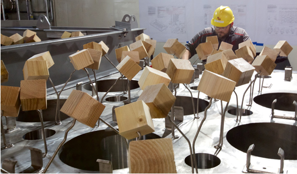 Vit Plant workers place wooden 4x4-inch blocks over steel rods as protection while they finish work on the glass-melter lids.