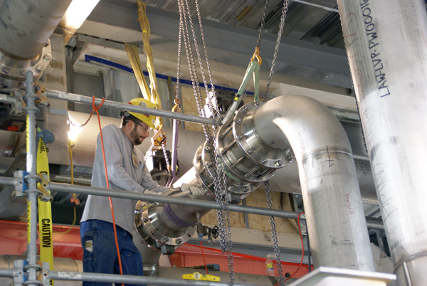 A pipefitter uses a wrench to tighten bolts on ventilation piping at the Low-Activity Waste Vitrification Facility.