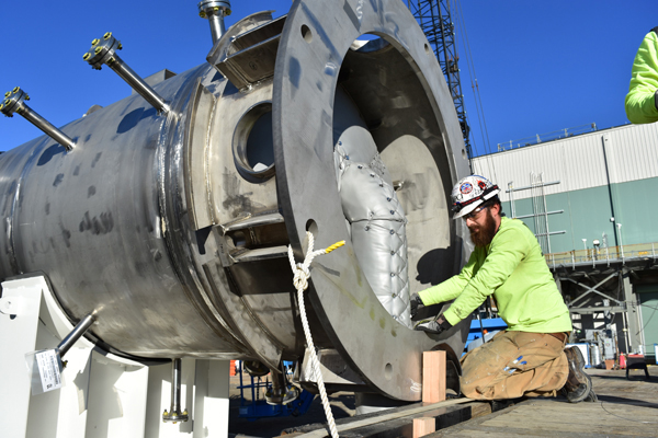 An insulator with Performance Contracting Inc., installs insulation on the underside of the caustic scrubber before it is lifted into the LAW Facility and placed in its design location.