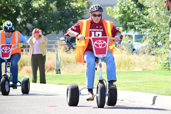 Vit Plant managers race on tricycles during a fundraiser for United Way