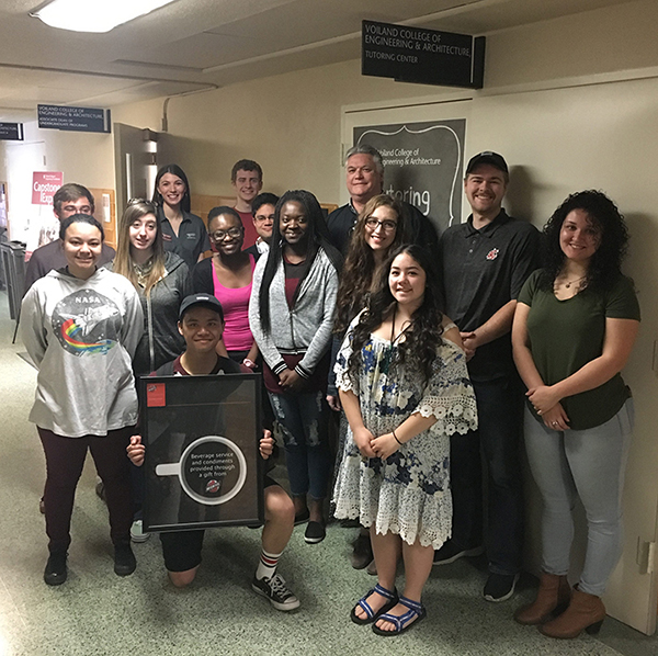 Scott Richey, area manager for One System, poses with students at Washington State University after delivering a donation to Voiland College of Engineering and Architecture