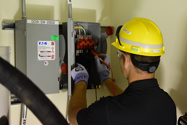 An electrician tests control panel switches in the Vit Plant's Analytical Laboratory.