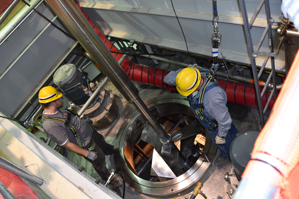 Workers install an agitator in a stainless steel vessel in the Low-Activity Waste (LAW) Vitrification Facility.