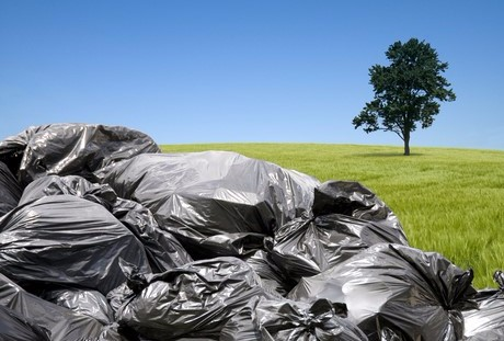 Pile of black garbage bags in a green field.