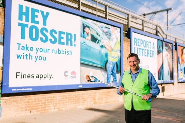 WSROC President, Cr Stephen Bali holds aluminium can in front of anti-littering billboard at Auburn train station.