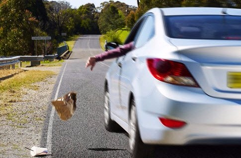 Person littering from a car whilst driving on a highway.
