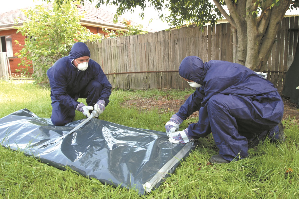 Asbestos removalists in hazmat suits covering asbestos fibro sheeting in plastic.