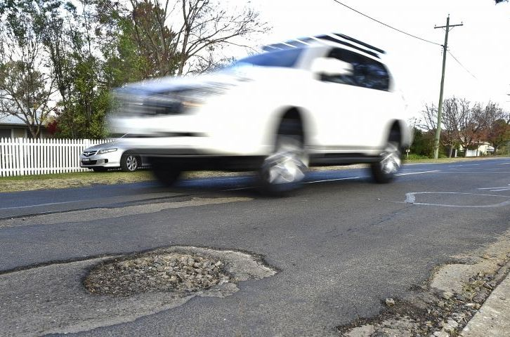 Car driving over pot-holed road