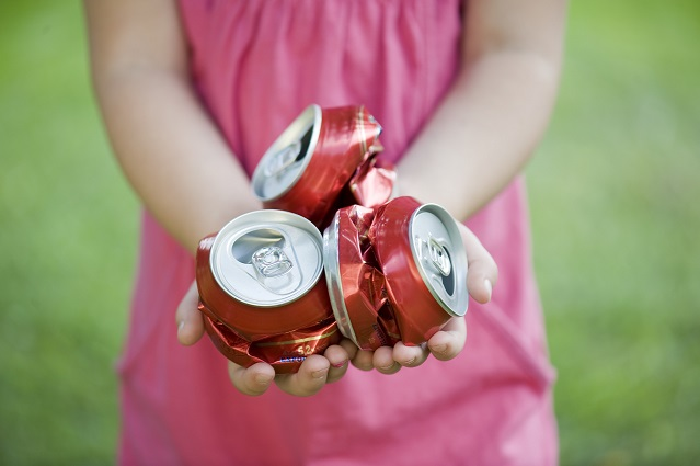 Child holding aluminium cans for recycling.