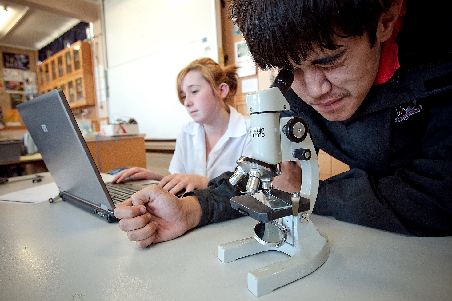 Students at a microscope and laptop