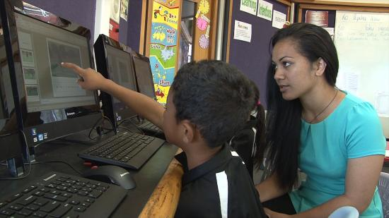 Student working on computer with teacher aide