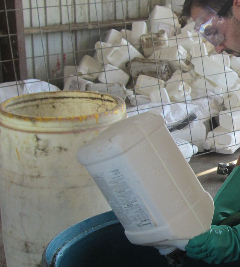 Wearing gloves and goggles to clean pesticide containers