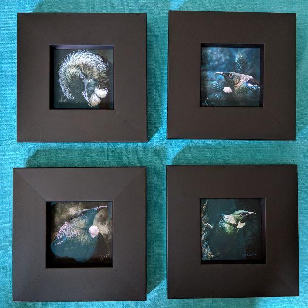 Photo of four TinyArt tūī pieces taken in unflattering light