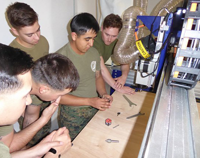 Hector, who used a ShopBot in his woodworking class in High School in Texas, shows other Marines how to change a bit.